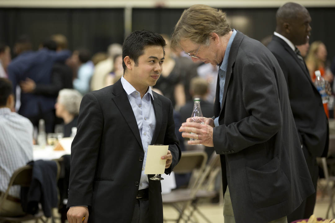 Suraj Karmacharya '14 of Kathmandu, Nepal, and Professor of Politics William Corlett chat as seniors join faculty to celebrate academic accomplishments of the Class of 2014 in the Clifton Daggett Gray Athletic Building. (Phyllis Graber Jensen/Bates College)