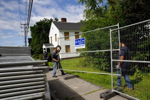 Workers erect fencing around the Campus Life Project site at Central and Campus avenues on July 29, 2014. (Phyllis Graber Jensen/Bates College)
