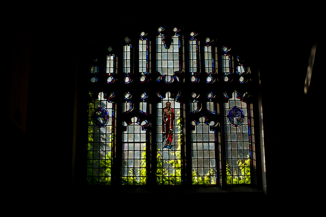 A stained glass portrait of Aristotle is lit by summer sunlight entering the Peter J. Gomes Chapel. (Phyllis Graber Jensen/Bates College)