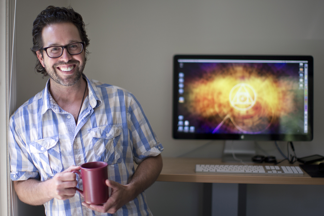 "Barry Costa, web designer with the Bates Communications Office, poses by his office computer whose monitor features his original vision art, ""a psychological exploration of an emotion or an idea."" (Phyllis Graber Jensen/Bates College)"