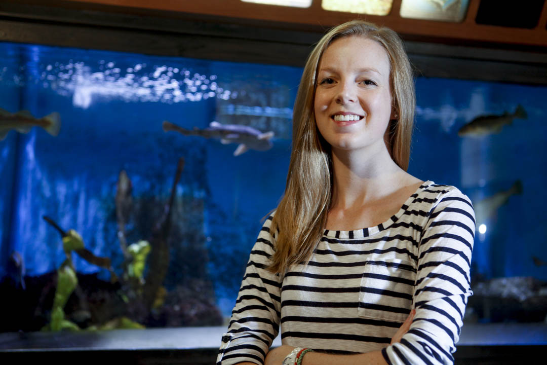 Kelly Simonson '15 of University Park, Texas, stands before a tank filled with various fish species at the Northeast Fisheries Science Center in Woods Hole, Mass., where she is a Bates Ladd Intern working on a project that seeks to understand better the sounds that fish, specifically cod, make. (Sarah Crosby/Bates College)