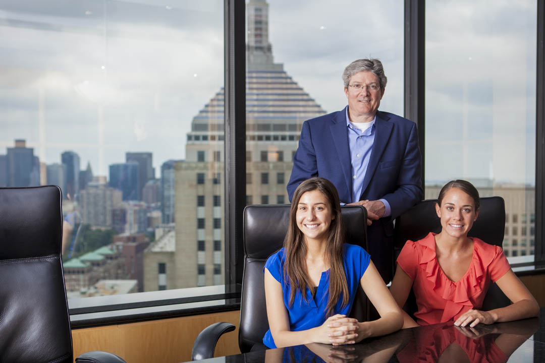 Bates Ladd Intern Daniela Rossi De Camargo '15 (left) of Walnut Creek, Calif., joins Ken Swan '82 and Kristen Poulin '12 for a portrait at their Lee Munder Capital Group headquarters in Boston's John Hancock Tower. Swan is Lee Munder CEO, and Poulin is a marketing associate. (Sarah Crosby/Bates College)