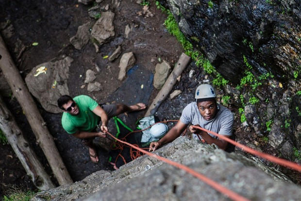 A few days before Convocation, Kwamae Delva '18 of Conley, Ga., begins his ascent of a rock wall in Rumney, N.H., as student leader Sean Enos '15 of Lynnfield, Mass., provides belay. The trip was one of many enjoyed by groups of first-years as part of AESOP, the Annual Entering Student Outdoor Program. (Sarah Crosby/Bates College)