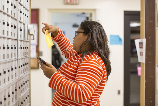 "Jacqueline Cooper '17 of Chicago pulls a yellow slip from her Chase Hall mailbox alerting her that she has a package awaiting her in the Package Center. Her prize? A DVD of ""The Great Gatsby"" that her mom sent her. (Phyllis Graber Jensen/Bates College)"