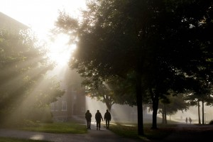 Foliage and fog go hand in hand on an early fall morning as students cross the Historic Quad. (Phyllis Graber Jensen/Bates College)