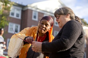 Laura Morrill P'15 of Frederick, Md., learns basket weaving from Atiya Haji. The Alumni Walk presentation was linked to a student's academic project looking at efforts by local Somali Bantuu women to market their crafts. (Phyllis Graber Jensen/Bates College)