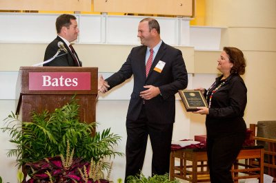 Stuart Abelson '97 accepts congratulations from Michael Lieber '92 after receiving the Bruce Stangle '70 Award for Distinguished Service to the Bates Community. Vice President Lisa Romeo '88 is at right. (Rene Minnis for Bates College)