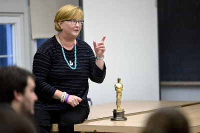 "Stacey Kabat '85 talks to students in a film criticism course taught by Jonathan Cavallero, assistant professor of rhetoric. She brought along her Academy Award because ""it's fun to hold it, so I always feel like sharing."" Students passed it around and, yes, it's heavy. (Phyllis Graber Jensen/Bates College)"