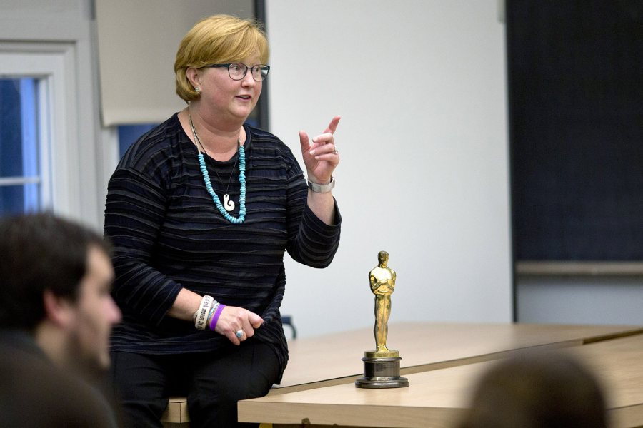 """Stacey Kabat '85 talks to students in a film criticism course taught by Jonathan Cavallero, assistant professor of rhetoric. She brought along her Academy Award because """"it's fun to hold it, so I always feel like sharing."""" Students passed it around and, yes, it's heavy. (Phyllis Graber Jensen/Bates College)"""