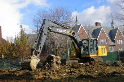 A power shovel nags a tree stump on the 45 Campus Ave. lot on Nov. 18, 2014. (Doug Hubley/Bates College)