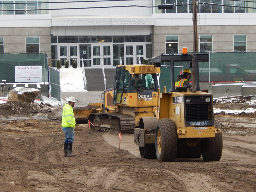 With the entrance to Lewiston Middle School in the background, workers for Gendron & Gendron prepare a parking area on the 65 Campus Ave. site. (Doug Hubley/Bates College)