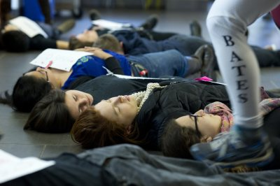 A student diner walks over protesters stretched out in front of the vegan bar. (Phyllis Graber Jensen/Bates College)