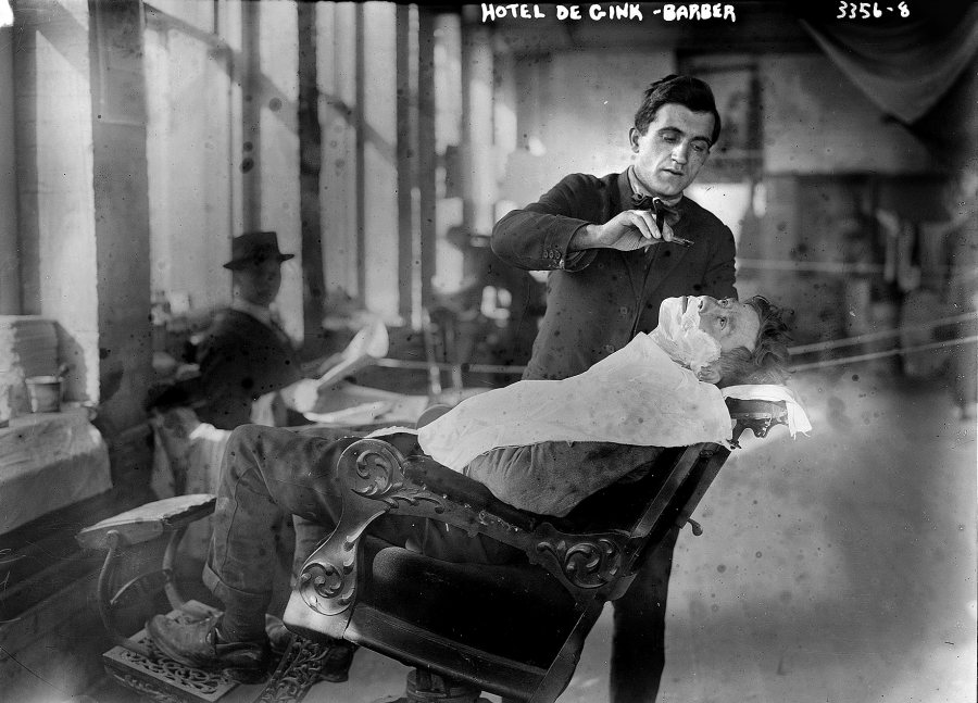 "A barber shaves a customer at Hotel de Gink, a hotel for the homeless in New York City, in 1915. Herzig's book notes that ""the advent of the bathroom facilitated shaving's passage from the public barber shop to the private space of the home.... he labors of hair removal were newly individualized and concealed."""