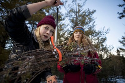 Bates students Kat Harling '17, left, and Grace Boueri '16 weigh twigs in Garcelon Bog, an im-portant wetland in Lewiston, as part of carbon-sequestration research carried out by a Bates College environmental studies course. (Sarah Crosby/Bates College) weigh a packet of twigs in Garcelon Bog, an ecologically significant wetland in Lewiston. The shrub clippings and other plant samples will be used to figure out how much carbon is sequestered in the bog in the project conducted in Holly Ewing's environmental studies course Scientific Approaches to Environmental Issues. (Sarah Crosby/Bates College)