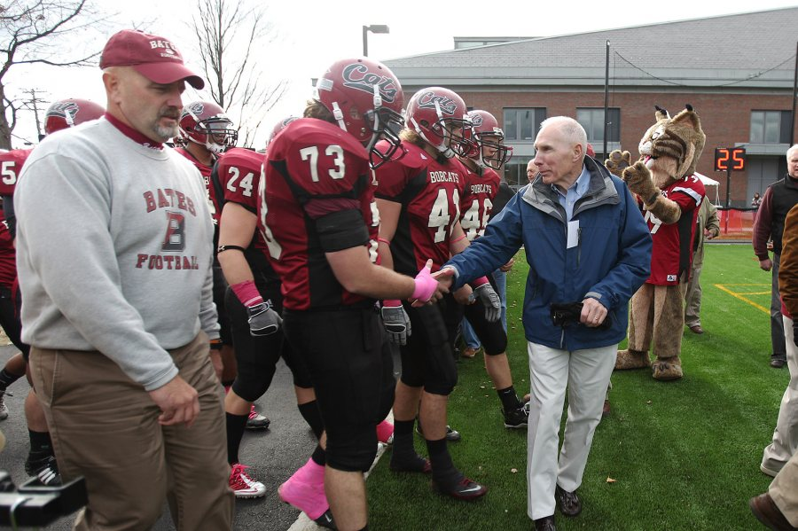 Paul Perry '57, a member of the 1956 Maine State Series champion football team, greets Brendan Murphy '11 as the Bobcat football team heads onto the field for its Homecoming game vs. Colby in 2010. (H. Lincoln Benedict '09)