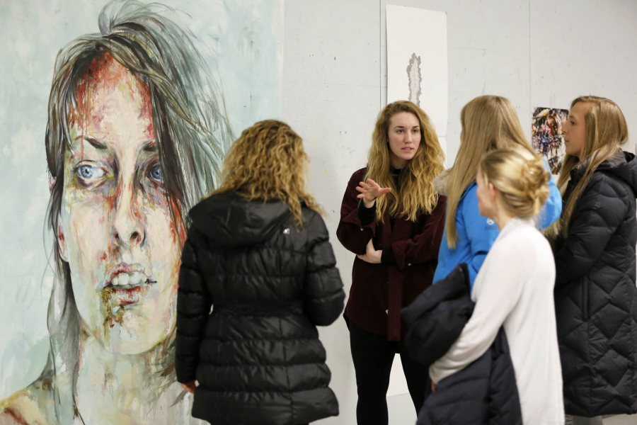 Student work in the visual, literary and performing arts takes center stage at Bates' annual Arts Crawl. In this 2015 image, studio art major Hannah McGrath '15 of Longmeadow, Mass., explains the process used by a fellow member of her thesis group, Ayse Ikizler '15 of Nashville, to create the painting seen at left. (Max Huang '18 for Bates College)
