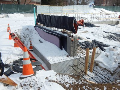 A wall foundation section sits on a spread footing at 65 Campus Ave. The black materials on the side of the concrete form are for moistureproofing. (Doug Hubley/Bates College)