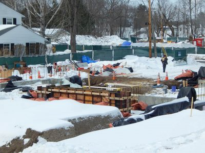 Wall foundation sections for the new student residence at 65 Campus Ave. The red-and-black tarp-like things are blankets that help concrete cure in the cold. (Doug Hubley/Bates College)