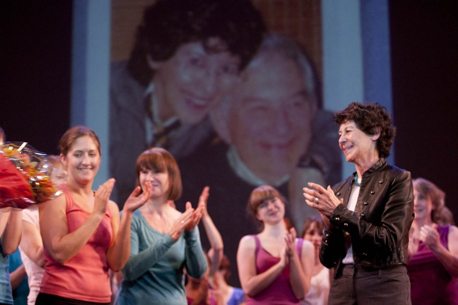 With an image of Marcy and the late Leonard Plavin in the background, retired Bates dance director Marcy Plavin applauds dancers during the April 30, 2011, dance alumni reunion. (Phyllis Graber Jensen/Bates College).