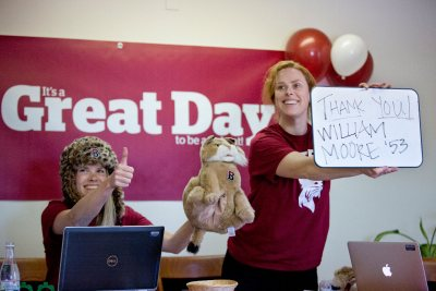 Bates staff thank a Great Day donor during the festive livestream on March 31, 2015. Rocking the bobcat hat at left is Cary Gemmer '07, director of alumni engagement, while Genevieve Leslie, director of Reunion fundraising and programming, holds the thank-you to donor William Moore '53. (Phyllis Graber Jensen/Bates College)