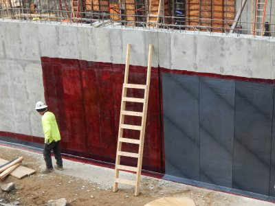 A waterproofing technician steps away from an exterior basement wall at 65 Campus Ave. on March 26, 2015. (Doug Hubley/Bates College)
