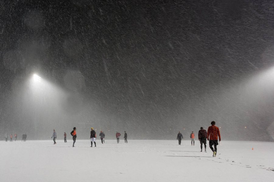 Seemingly oblivious to the early April snow, ultimate frisbee players practice on Garcelon Field. (Josh Kuckens/Bates College)