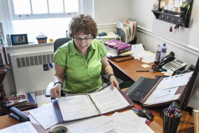 Claire Schmoll, executive assistant to President Spencer, prepares the formularies -- compilations of all the Commencement speeches -- in her Lane Hall office. (Josh Kuckens/Bates College)