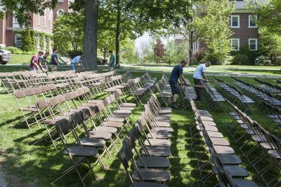 Facility Services workers use boards to set the  proper distance between rows of Commencement 2015 seating. (Josh Kuckens/Bates College)