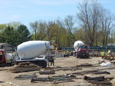 Concrete mixers ready to place foundation footings for the 55 Campus Ave. student residence on May 7, 2015. (Doug Hubley/Bates College)