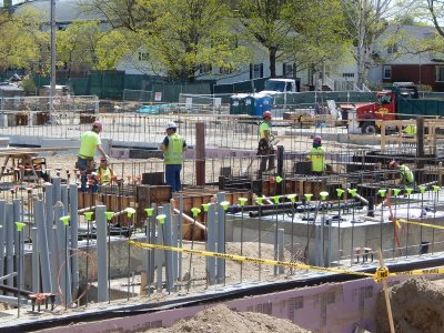With gray conduits for electrical, telecom and data service in the foreground, workers build a form for concrete footings at 55 Campus Ave. on May 7, 2015. (Doug Hubley/Bates College)