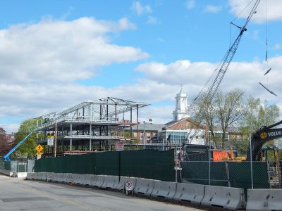 "With a ""Christmas tree"" -- multiple pieces of steel in one lift -- dangling from the crane, the framework of 65 Campus Ave. is shown from the west on May 13, 2015. (Doug Hubley/Bates College)"