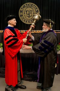 Professor of Sociology Sawyer Sylvester, who as senior member of the faculty was the longtime bearer of the college mace at ceremonial events, handed the mace over to his successor, Charles Franklin Phillips Professor of Economics Michael Murray at Commencement 2015. (Phyllis Graber Jensen/Bates College)