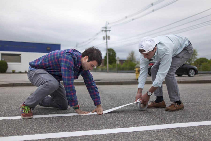 Matthew Winter '18 of New York City and Brendan Yucel '18 of Boston lay down lines for a demonstration bike lane on Oxford Street in Lewiston on May 20. They're students in an urban planning Short Term course taught by Mike Lydon '04. (Josh Kuckens/Bates College)