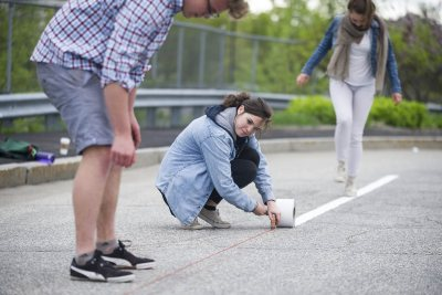 Theresa Seel '18 of Darmstadt, Germany, helps classmates put down lines for a demonstration bike lane on Oxford Street in Lewiston on May 20. The project was part of a Short Term urban planning course taught by Mike Lydon '04. (Josh Kuckens/Bates College)