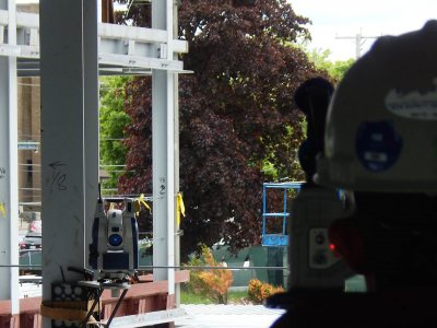 "The Trimble ""total station,"" fastened to a beam at left, guides the surveyor (back to camera) as he marks utilities sites at 65 Campus Ave. on June 3, 2015. (Doug Hubley/Bates College)"