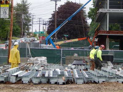 Holding onto the ends of cables attached to the construction crane, steelworkers look for the next pieces to be lifted into place at 55 Campus Ave. on June 2, 2015, the first day of steel work. (Doug Hubley/Bates College)