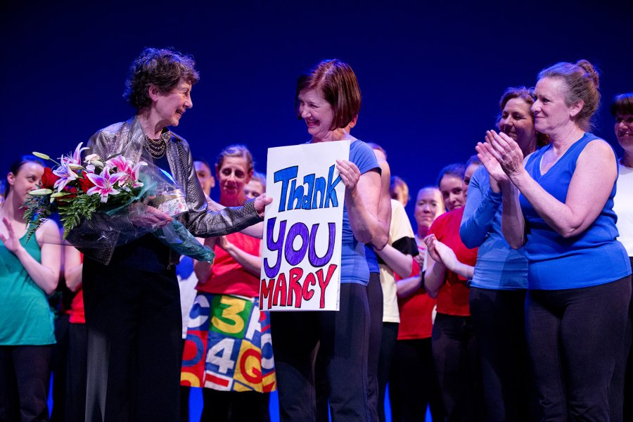 Geri FitzGerald '75 holds a thank-you sign for Marcy Plavin at the conclusion of the 2015 dance reunion concert in Schaeffer Theatre. (Phyllis Graber Jensen/Bates College)