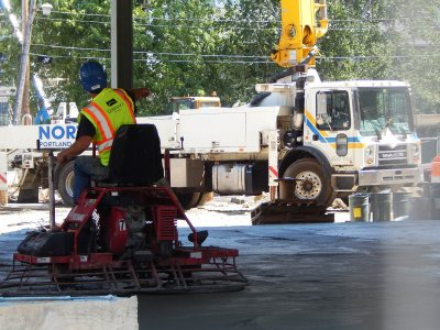 Concrete reality: More fun with the ride-on trowel -- one of three that were smoothing fresh concrete on the ground floor of 55 Campus Ave. on July 16, 2015. (Doug Hubley/Bates College)