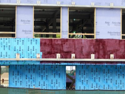 A bouquet of structural wall treatments: lavender gypsum board, Dodger blue vapor barrier and the burgundy adhesive that holds them together. 65 Campus Ave. on July 24, 2015. (Doug Hubley/Bates College)
