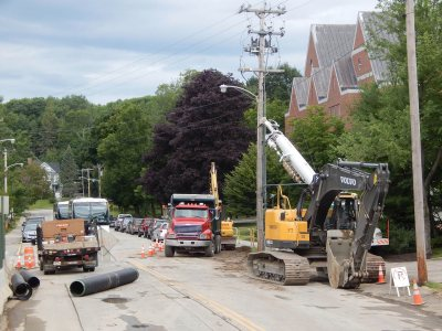 This July 24 image depicts a familiar sight at Bates in July 2015: utility crews performing open-tar surgery on Campus Avenue while traffic finds a way around. (Doug Hubley/Bates College)
