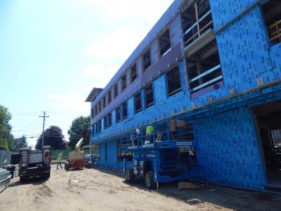 Turning blue on a hot day: Insulation technicians apply a stick-on blue vapor barrier to the north wall of 65 Campus Ave. on July 28, 2015. (Doug Hubley/Bates College)