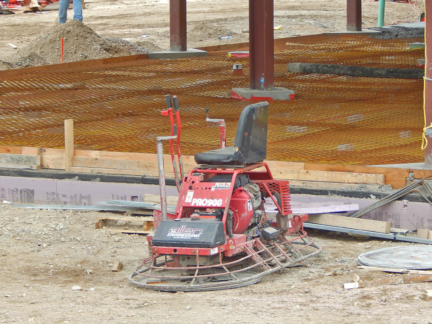 If your concrete is bumpy, it's time to throw in the trowel — the Allen Engineering Pro900 ride-on trowel, that is. Photographed at 65 Campus Ave. on June 12, 2015. The rusty material in the background is steel mesh reinforcement for the concrete floor slabs. (Doug Hubley/Bates College)