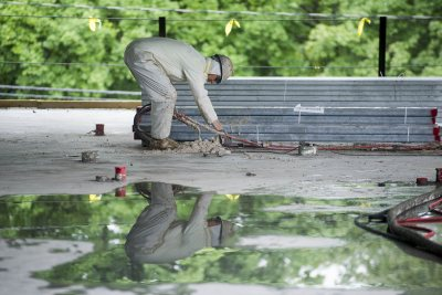 A fireproofing technician adjusts his applicator at 65 Campus Ave. on July 1, 2015. (Josh Kuckens/Bates College)