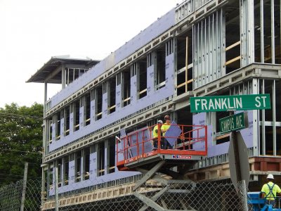 Workers install wallboard at the new student residence at 65 Campus Ave. on July 9, 2015. (Doug Hubley/Bates College)