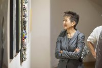 "The NEA's  Jane Chu admires a piece the Bates Museum of Art exhibition ""Maine Collected."" (Josh Kuckens/Bates College)"