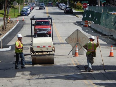 For much of July and August, 2015, Campus Avenue was closed for utilities work related to the Campus Life Project. In this image from Aug. 13, pavers tamp down new asphalt. (Doug Hubley/Bates College)