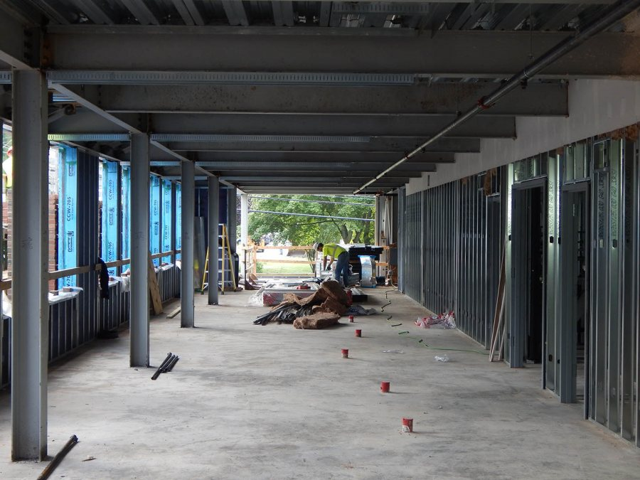 A wall framer at work on the second floor of 65 Campus Ave. on Aug. 26, 2015. The enclosed space at right is part of the building core. Visible beyond are the grounds of Lewiston Middle School. (Doug Hubley/Bates College)