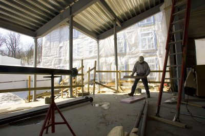 A carpenter at work in the fireplace lounge at the new student housing. (Phyllis Graber Jensen/Bates College)