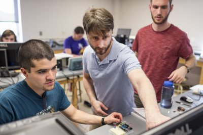 "Assistant Professor of Physics Travis Gould (center) works with Armando Morales Urrutia '16 (left) of Fraijanes, Guatemala and Daniel Paseltiner '16 of Devon, Pa., during the Short Term course ""Microcontroller Laboratory."" (Josh Kuckens/Bates College)"