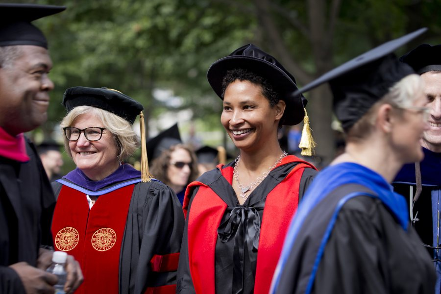 Bates College President Clayton Spencer and Harvard professor Danielle Allen watch as faculty pass before them during Bates' Convocation procession on Sept. 8, 2015. Allen, author of a celebrated study of the U.S. Declaration of Independence, gave Bates' Convocation address. (Phyllis Graber Jensen/Bates College)